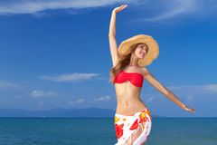 Beautiful woman full of the joys. Beautiful lively woman full of the joys of life twirling with her arms in the air in a colourful bikini and sarong against an Stock Image