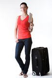 Tourist woman ready for departure. Beautiful woman full-length standing next to her suitcase, holding in hand a ticket- ready for her summer travel. Shot in Royalty Free Stock Photo