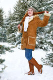Beautiful woman full length on winter outdoor, snowy fir trees in forest, long red hair, wearing a sheepskin coat Royalty Free Stock Photography