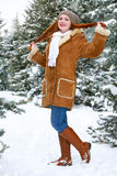Beautiful woman full length on winter outdoor, snowy fir trees in forest, long red hair, wearing a sheepskin coat Royalty Free Stock Photos