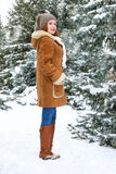 Beautiful woman full length on winter outdoor, snowy fir trees in forest, long red hair, wearing a sheepskin coat Royalty Free Stock Photo