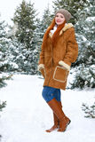 Beautiful woman full length on winter outdoor, snowy fir trees in forest, long red hair, wearing a sheepskin coat Stock Photos