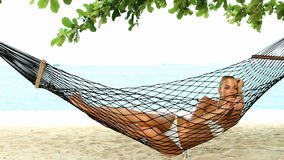 Beautiful woman full of vitality reclining suntanning in a hammock stock video