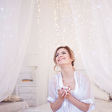 Beautiful woman  fun laughs in the bedroom drinking coffee. A girl holds  Cup, enjoy a drink. Square crop Royalty Free Stock Photography