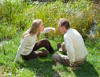 The beautiful woman for fun threatens to knock the man on a nose in the summer on a grass at the lake Stock Image