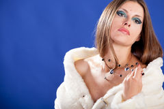 Beautiful woman in fur on blue background Stock Photo