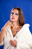Beautiful woman in fur on blue background Stock Photography