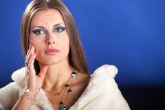 Beautiful woman in fur on blue background Royalty Free Stock Images