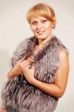 Beautiful woman in a fur coat. Studio shot Stock Image