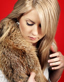 Beautiful woman in a fur coat. Over red background Royalty Free Stock Images
