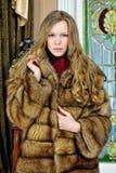Beautiful woman in fur coat. Portrait of the beautiful woman in fur coat. The luxurious classical interior Stock Image
