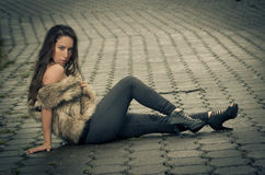 Beautiful woman in a fur coat. Sitting on the street Royalty Free Stock Photos