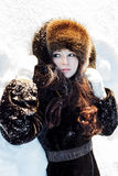 Beautiful woman in a fur coat and fur hat on a white snowy background Royalty Free Stock Images