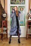 Beautiful woman in fur coat in the interior. Portrait of the beautiful woman in fur coat. The luxurious classical interior Stock Image