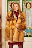 Beautiful woman in fur coat in the interior. Portrait of the beautiful woman in fur coat. The luxurious classical interior Stock Images