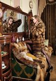 Beautiful woman in fur coat in the interior Stock Photos