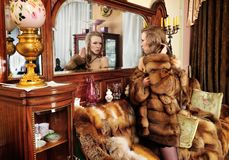 Beautiful woman in fur coat in the interior Stock Image
