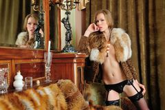 Beautiful woman in fur coat in the interior Stock Photos