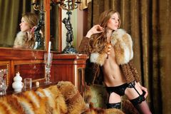 Beautiful woman in fur coat in the interior Royalty Free Stock Images