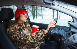 Beautiful woman in a fur coat and red hat with coffee to go driv Stock Images