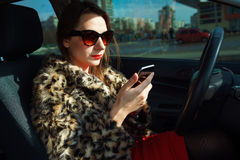 Beautiful woman in a fur coat with red lips using smartphone in Royalty Free Stock Photography