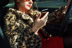 Beautiful woman in a fur coat with red lips using smartphone Stock Image