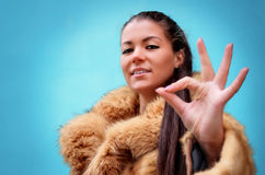Beautiful woman in a fur coat showing sign ok Stock Photos