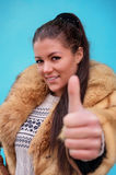 Beautiful woman in a fur coat showing thumb up. Beautiful woman in a fur coat against blue background showing thumb up Royalty Free Stock Image