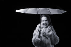 Beautiful woman with fur coat standing in rain under an umbrella Stock Photo
