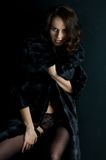 Beautiful woman in a fur coat and stockings. Stock Photography