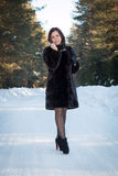 Beautiful woman in a fur coat in the winter forest. Woman in a fur coat in the winter forest Stock Photography