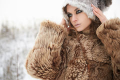 Beautiful woman in fur hat.outdoor. Fashion beauty outdoor portrait of young woman in fur hat. beautiful model girl in snow winter forest.wild nature Stock Photos