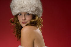 Beautiful woman with fur hat on red background Stock Images