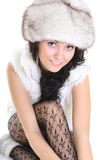Beautiful woman in fur hat  sitting. Young attractive woman in fur hat isolated over white background Stock Photography