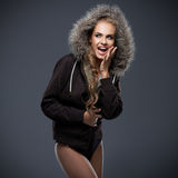 Beautiful woman in a fur trimmed hood. Beautiful woman in a winter jacket with a fur trimmed hood posing with bare legs against a grey studio background Royalty Free Stock Image