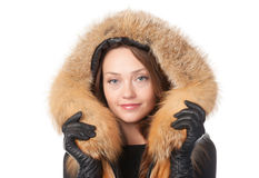 Beautiful woman in fur trimmed jacket. Beautiful smiling woman in fur trimmed jacket with hood keeping warm against the winter cold isolated on white Royalty Free Stock Photography