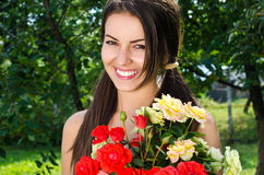 Beautiful woman in the garden with flowers. Royalty Free Stock Image