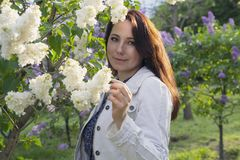 Beautiful woman in garden among the lilacs stock image
