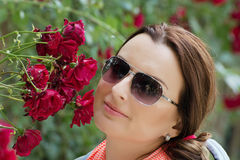 Beautiful woman in garden with red roses Stock Images