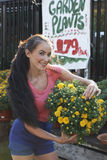 Beautiful Woman At Garden Shop. Attractive young woman holding large potted plant at gardening store in front of sales sign Royalty Free Stock Photo