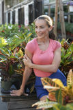 Beautiful Woman At Garden Shop. Attractive young woman leaning against display of large potted plants at gardening store on sunny day Stock Images