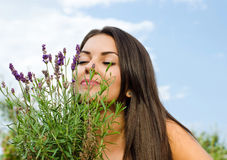 Beautiful woman in the garden smelling flowers. stock image