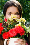 Beautiful woman in the garden smelling flowers. Royalty Free Stock Photo