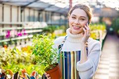 Beautiful woman gardener talking on mobile phone in orangery Stock Photo