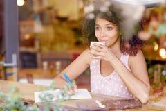Beautiful woman gazing out a coffee window daydreaming Stock Photo