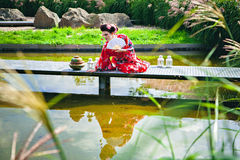 Beautiful woman in geisha costume in the garden on the bridge Royalty Free Stock Images
