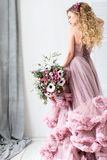 Beautiful woman with a gently pink bouquet of flowers. royalty free stock image