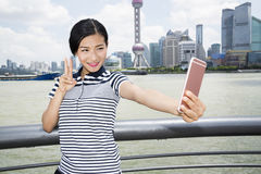 Beautiful woman gesturing peace sign while taking selfie through smart phone against Pudong skyline Royalty Free Stock Image