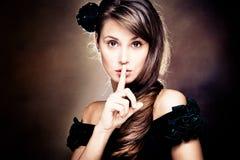 Beautiful woman gesturing silence. Beautiful young woman gesturing silence, studio shot Stock Photos
