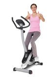 Beautiful woman gesturing thumbs up on stationary bike Stock Photography